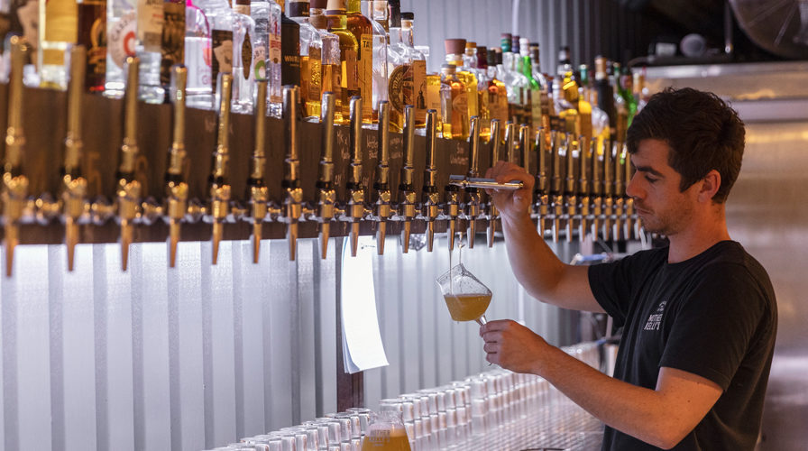 Employee pouring beer at Mother Kellys