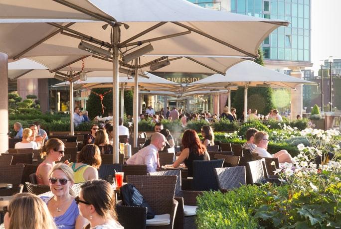 people sitting outside Riverside pub in summer landscape
