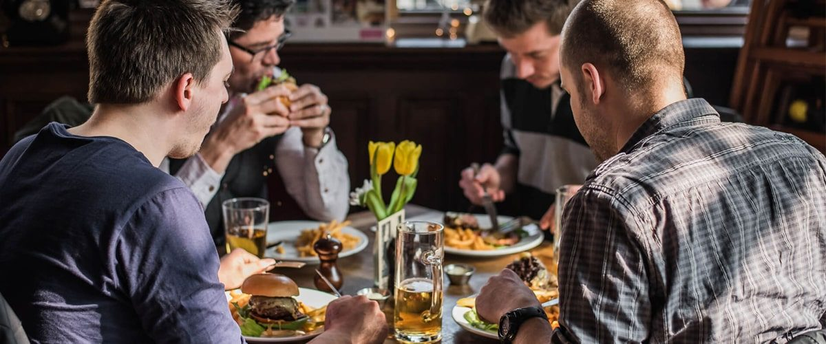 The Black Dog pub customers eating burgers with pints