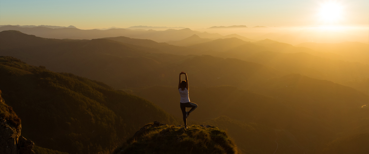 Women in a yoga post on top of a mountain