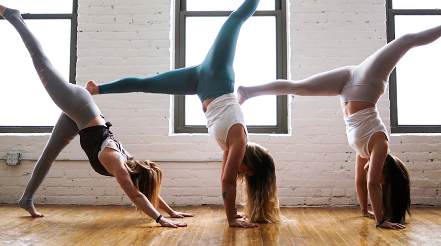 Embody Vauxhall yoga improvers class - 3 people in upside down yoga poses wide angle